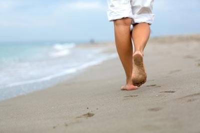 person walking barefoot on beach